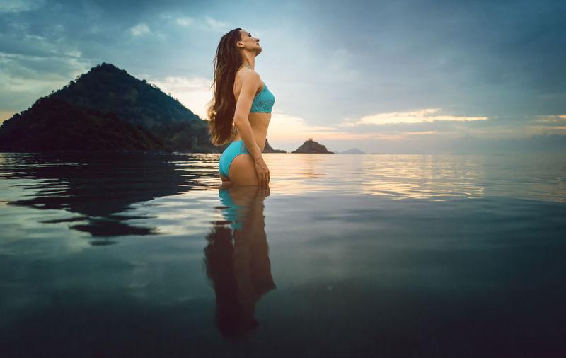 Woman Wearing Bikini Standing In Sea Against Sky