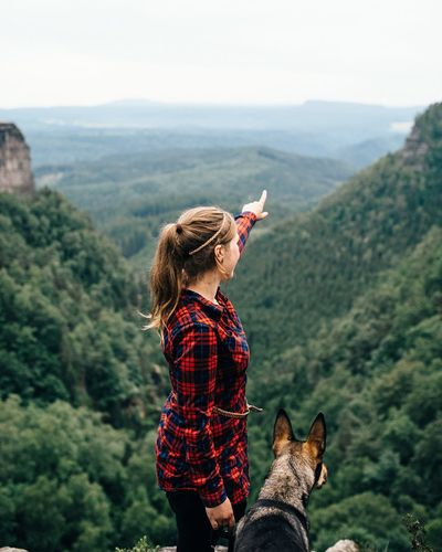 Side View Of Woman Pointing While Standing With Dog Against Mountains