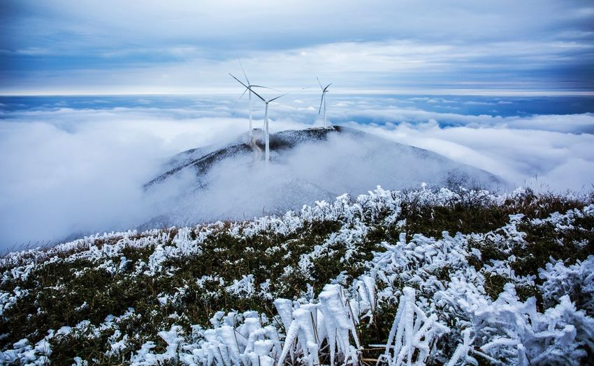 Windmills on mountain over clouds during winter