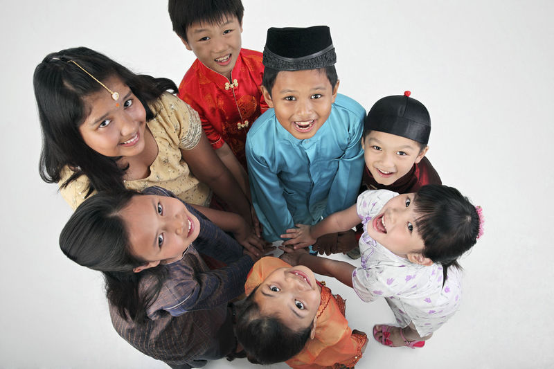 malaysian with traditional clothing looking at camera Fun Happiness Indian Innocence Patriotism Standing Teamwork Traditional Clothing Chinese Elementary Age Friendship Front View Harmony High Angle View Look Up Malay Malaysia Mixed Race Multiracial  Positive Emotion Smiling Studio Shot Togetherness United White Background