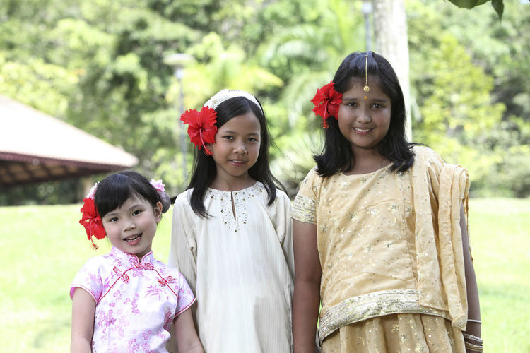 malaysian girls with traditional clothing wear national flower Indian Innocence Patriotism Traditional Clothing Bunga Raya Childhood Chinese Cute Different Cultures Elementary Age Flower Friendship Group Of People Harmony Hibiscus Lifestyles Malay Malaysia Malaysia Flag Merdeka Mixed Race Multiracial  Outdoors Togetherness United