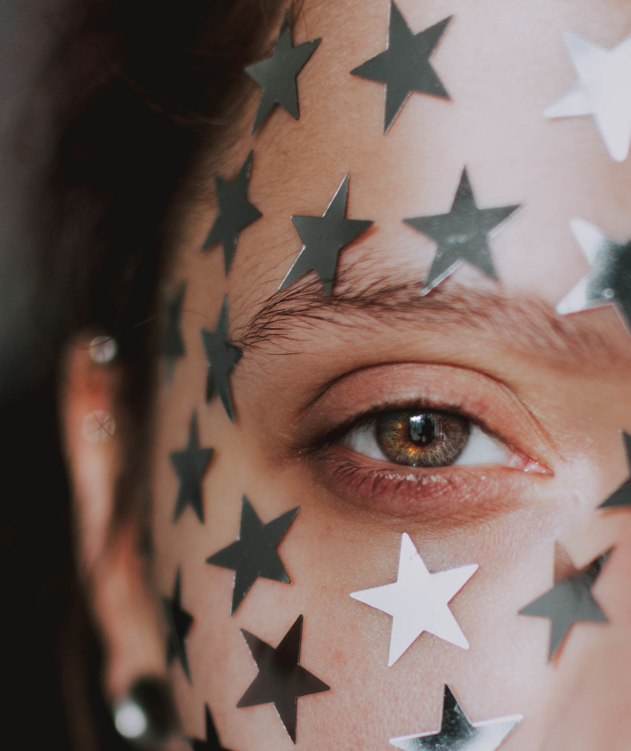 Close-up portrait of young woman with stars on face
