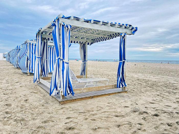 Lifeguard chair on beach against blue sky