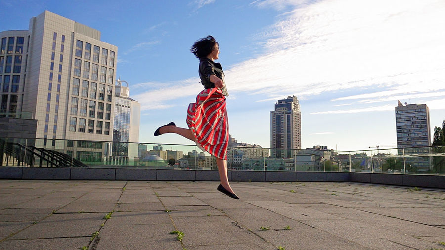 Woman jumping with cityscape against sky