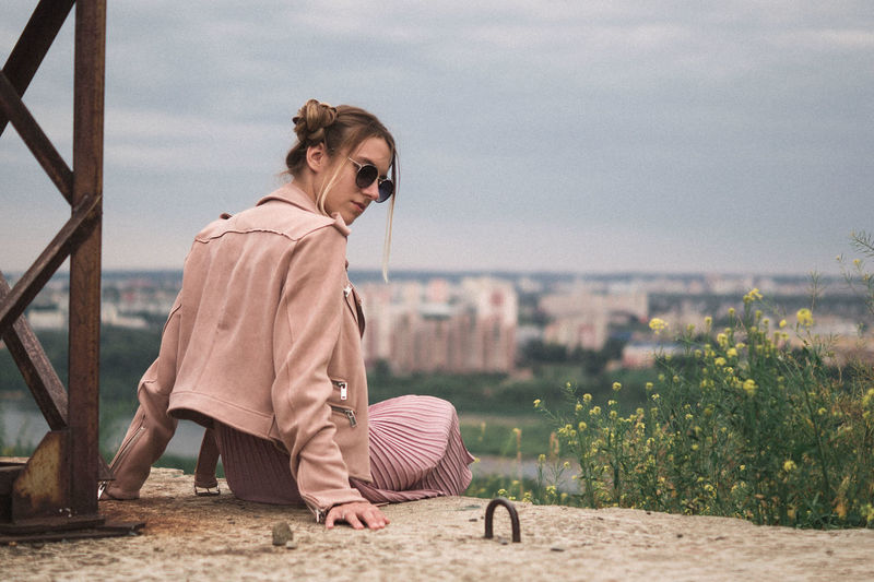 Woman wearing sunglasses sitting against sky