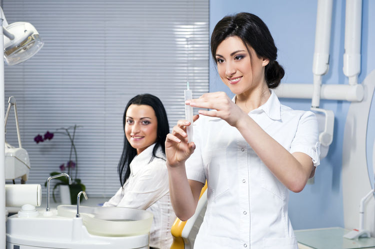 Attractive woman dentist with medical syringe and smiling patient in the dental clinic Anaesthesia Dental Dentist Dentistry Doctor  Injection Looking At Camera Medicine Nurse Uniform Assistant Beautiful Woman Brunette Caucasian Cheerful Dental Clinic Indoors  Medical Orthodontic Patient Professional Occupation Smiling Syringe Teeth Women