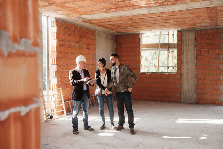 Agent explaining couple while standing in construction building