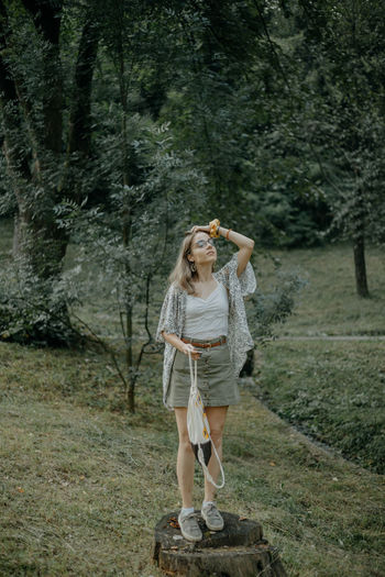 Full length of a woman standing in forest