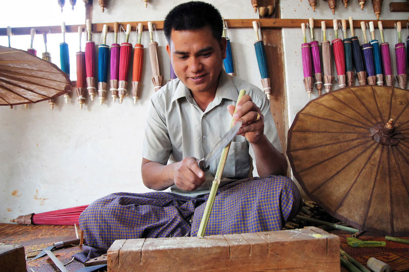 Umbrella maler, Off the beaten track, in and around Taunggy, Shan State, Myanmar Adult Adults Only Art And Craft Art Studio Artist Casual Clothing Concentration Craftsperson Day Holding Indoors  Instrument Maker Music Myanmar One Man Only One Person Only Men People Real People Sitting Skill  Wood - Material Workbench Workshop Young Adult