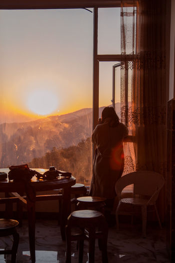 Rear view of man standing by window at sunset
