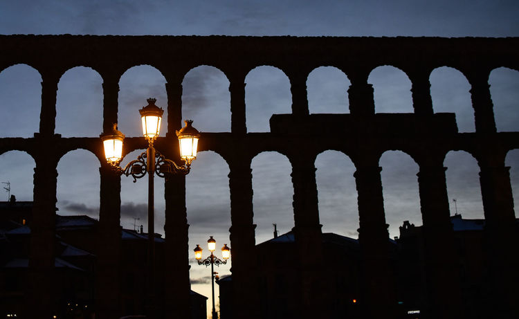 A view of the aqueduct of Segovia during sunset and night Acueducto Acueduct Ancient Ancient Civilization Arch Architectural Column Architecture Building Exterior Built Structure Day History Illuminated Indoors  Light And Shadow Night Old Ruin Real People Roman Romanic Romanic Architecture Segovia Sky Streetlight Sunset Travel Destinations