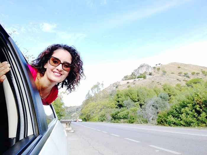 Portrait of woman traveling in car on road