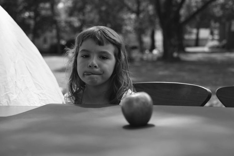 Girl looking at apple on table