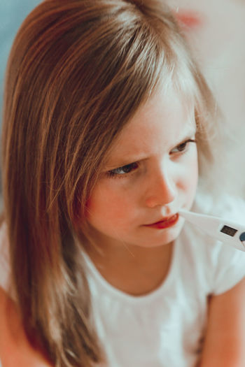 Close-up of girl with thermometer in mouth at home