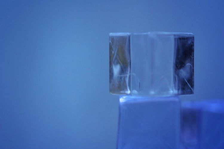 Close-up of ice cubes against blue background