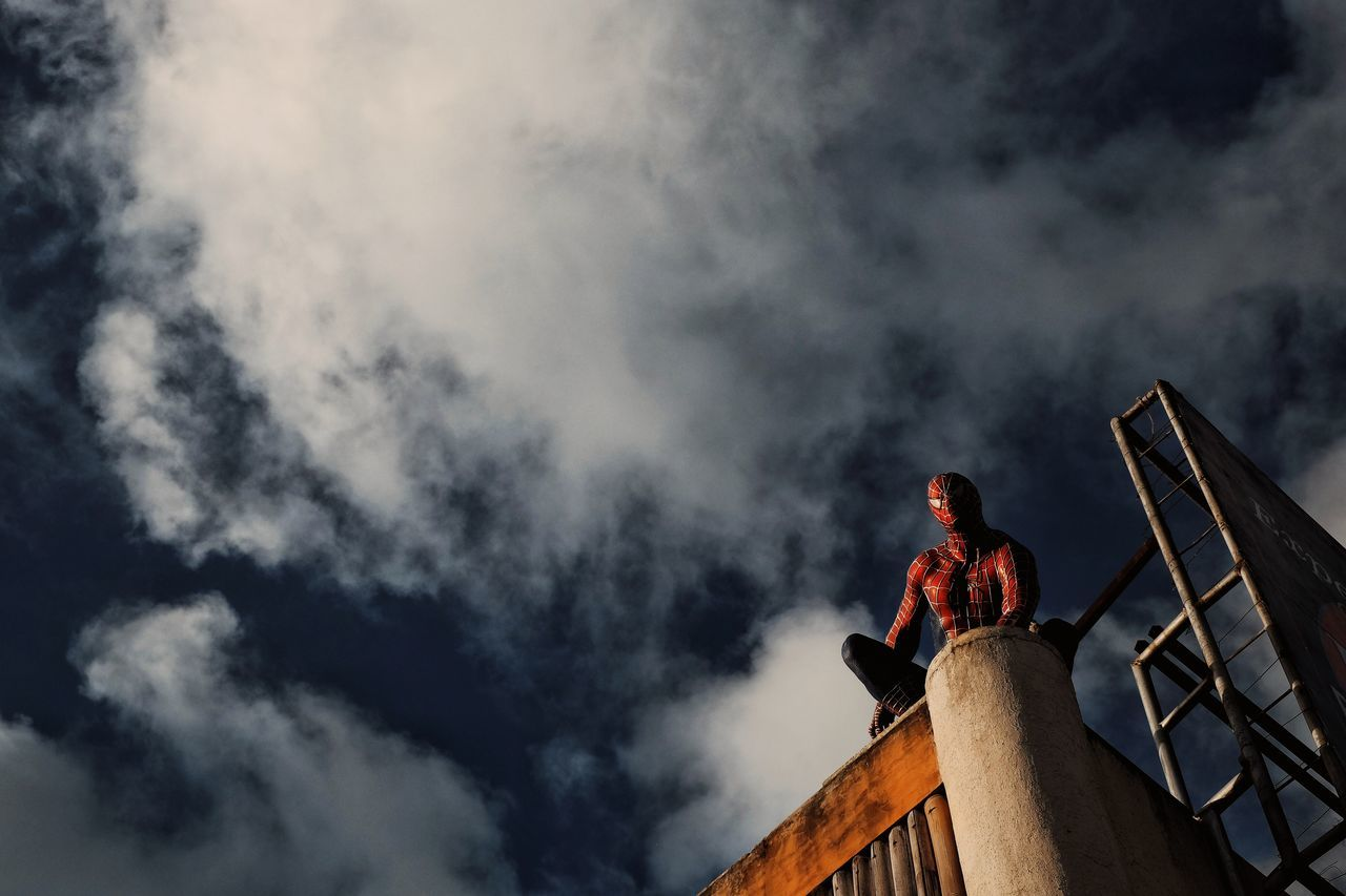 LOW ANGLE VIEW OF MAN STANDING IN SKY
