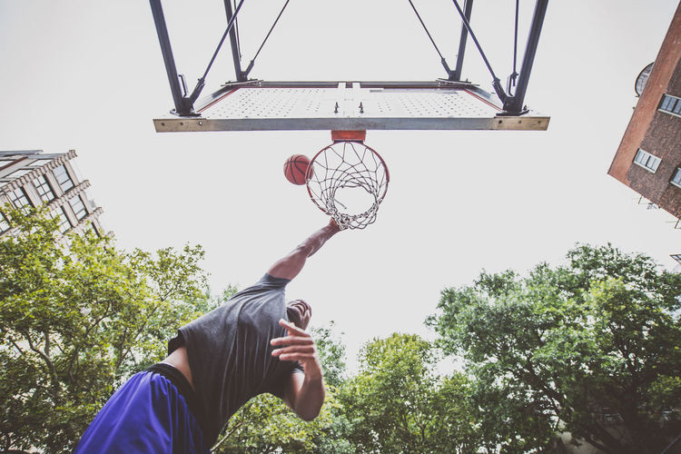 Low angle view of young man playing basketball