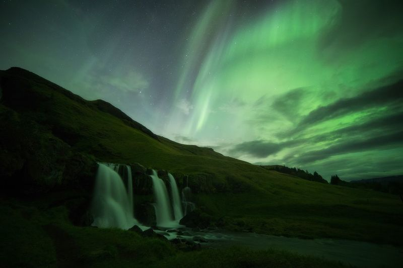 Northern lights above the waterfall in Iceland Mountain Nature Beauty In Nature Outdoors Night Scenics No People Sky Landscape Galaxy
