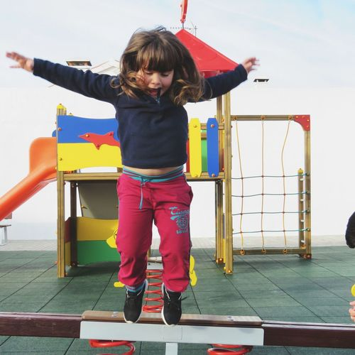 Full length of girl jumping at playground