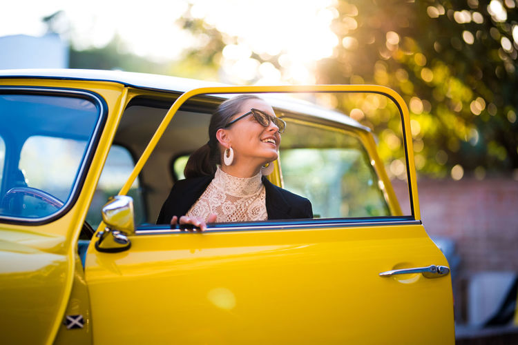 MiniCooper Glamour Style And Fashion Fashion Model Sonrisa Lifestyles Smiling Drive Glass Working Mode Of Transportation Girl Happiness Young Adult Young Women Leisure Activity Car Door Hairstyle Yellow Car Real People One Person Women
