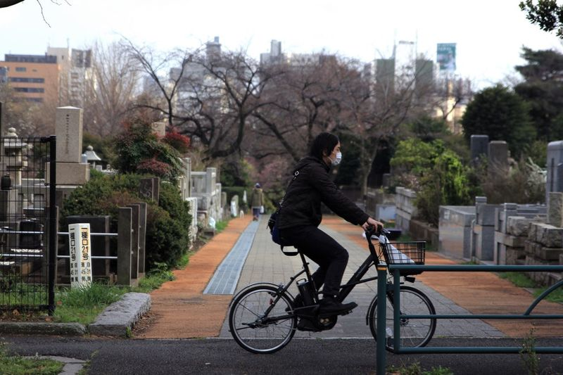 Side view of man riding bicycle against plants