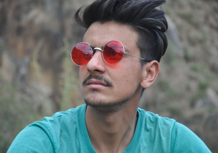 Portrait of young man sitting outside with wearing sunglasses and looking sideways