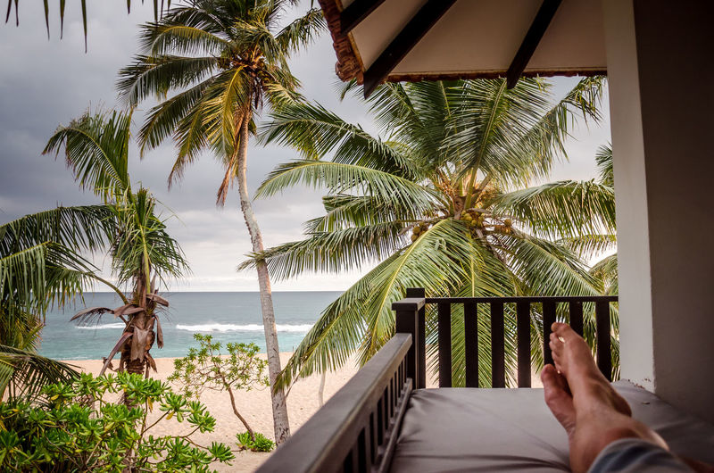 Low section of person relaxing on bed at beach