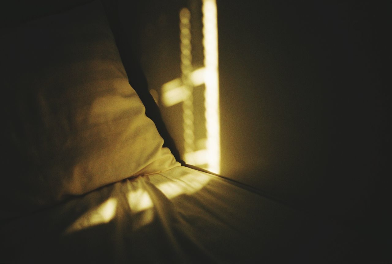 Sunlight falling on wall and bed