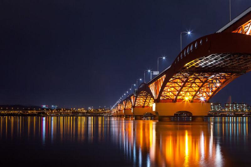 Illuminated seongsan bridge over han river against sky