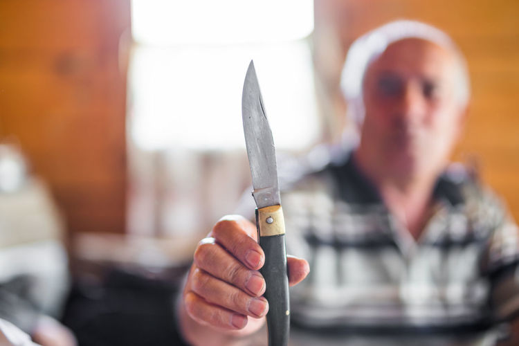 Mature man holding knife at home