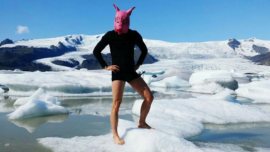 Man wearing pig mask while standing on frozen lake