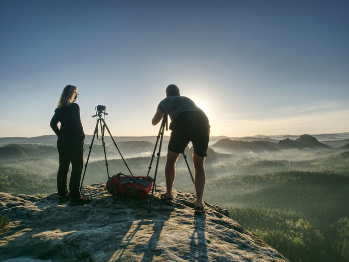 Creative artists stay at cameras on tripods. hikers and photo enthusiasts work together on cliff
