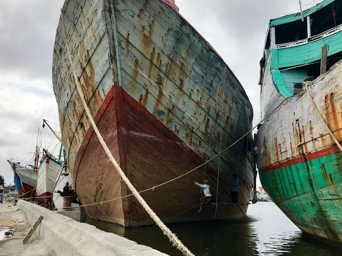 Low angle view of old ships moored on sea against sky