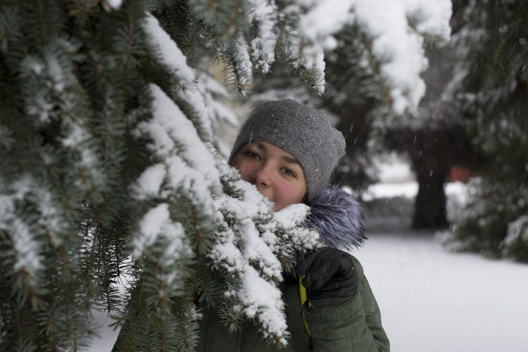 Portrait of girl standing by pine tree during winter