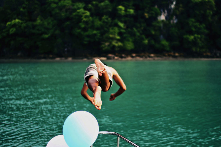 Shirtless man diving into lake