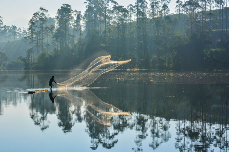 Reflection of man in lake against trees in forest