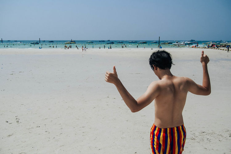 Rear view of shirtless man with thumbs up sign at beach