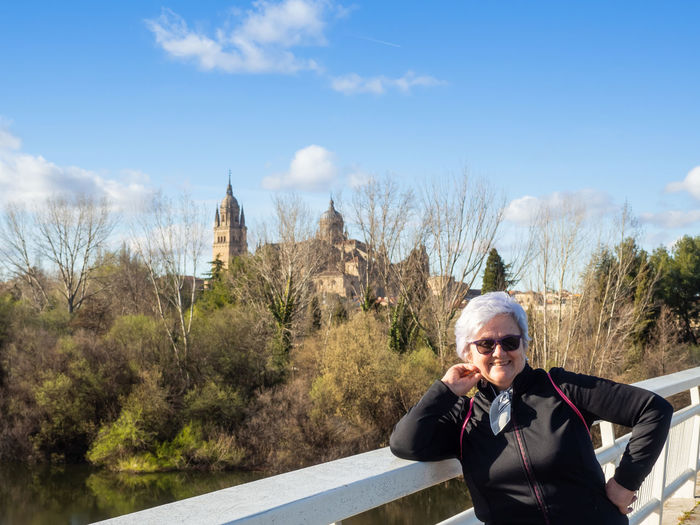 Portrait of smiling senior woman standing on footbridge over river during sunny day