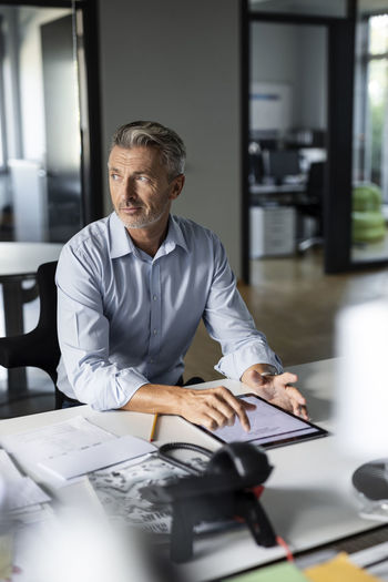Midsection of man using smart phone while sitting on table