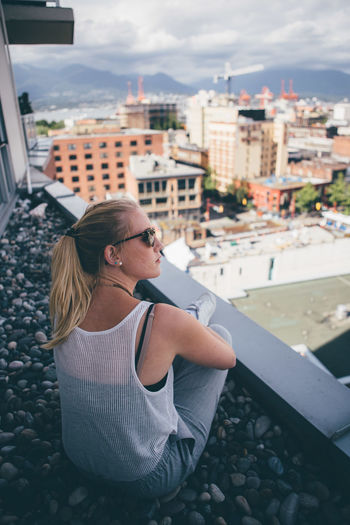 High Angle View Of Woman Wearing Sunglasses While Sitting On Building Terrace