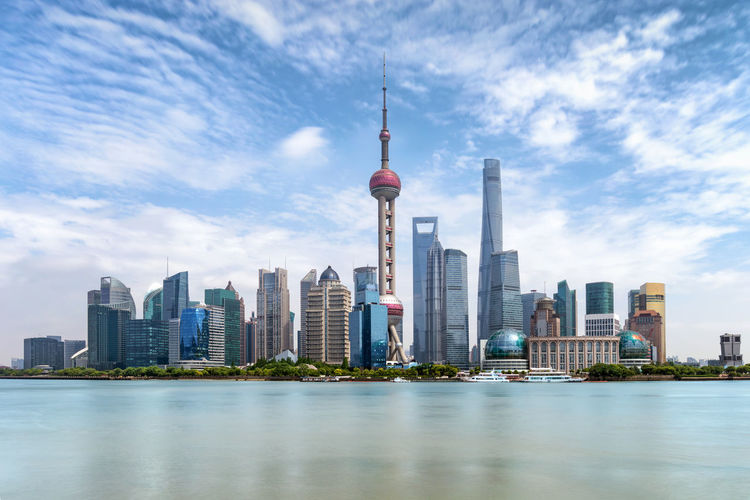 The modern skyline of Shanghai, China, on a sunny day Modern Shanghai Tourist Attraction  Travel Architecture Attraction Building Building Exterior Built Structure China Chinese City Cloud - Sky Landscape Modern Oriental Pearl Tower Sky Tall - High Tourism Tower Travel Travel Destinations Urban Skyline Water Waterfront