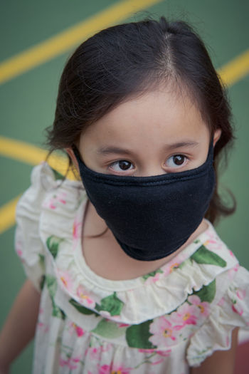 Close-up of cute girl wearing mask