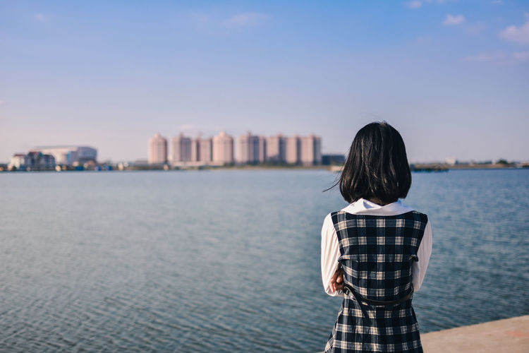 Rear view of young woman looking at sea against blue sky