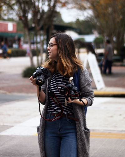 Canon One Person Real People Camera - Photographic Equipment Young Adult Leisure Activity Photographer Young Women Photographing Street Holding Standing Digital Single-lens Reflex Camera Technology Women Day Lifestyles Casual Clothing Outdoors Photography Themes