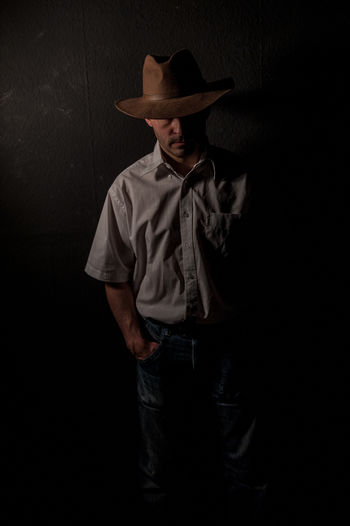 Man Wearing Hat Standing With Hand In Pocket Against Wall In Darkroom