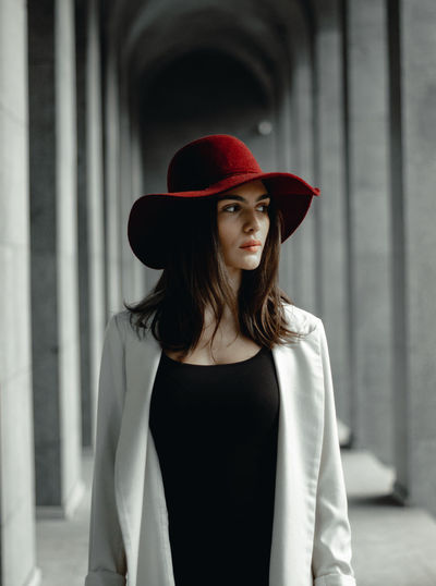 Young woman wearing hat while looking away standing in corridor