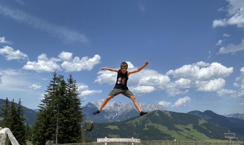 Full length of person jumping against sky
