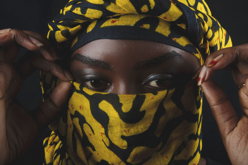 Close-Up Of Woman Wearing Scarf Against Black Background