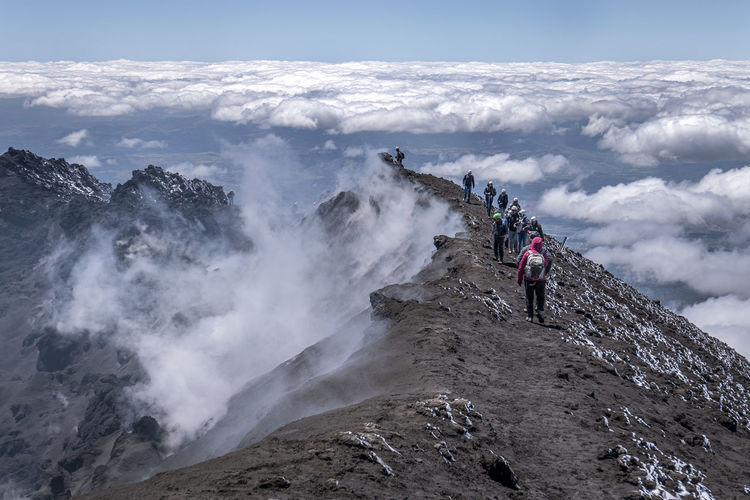 Panoramic view of people on mountain against sky