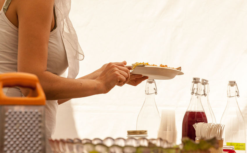 Midsection of woman taking food in buffet